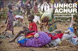 Un niño sursudanés se sienta sobre las pertenencias que su familia ha traido a Uganda tras huir de su casa. ACNUR